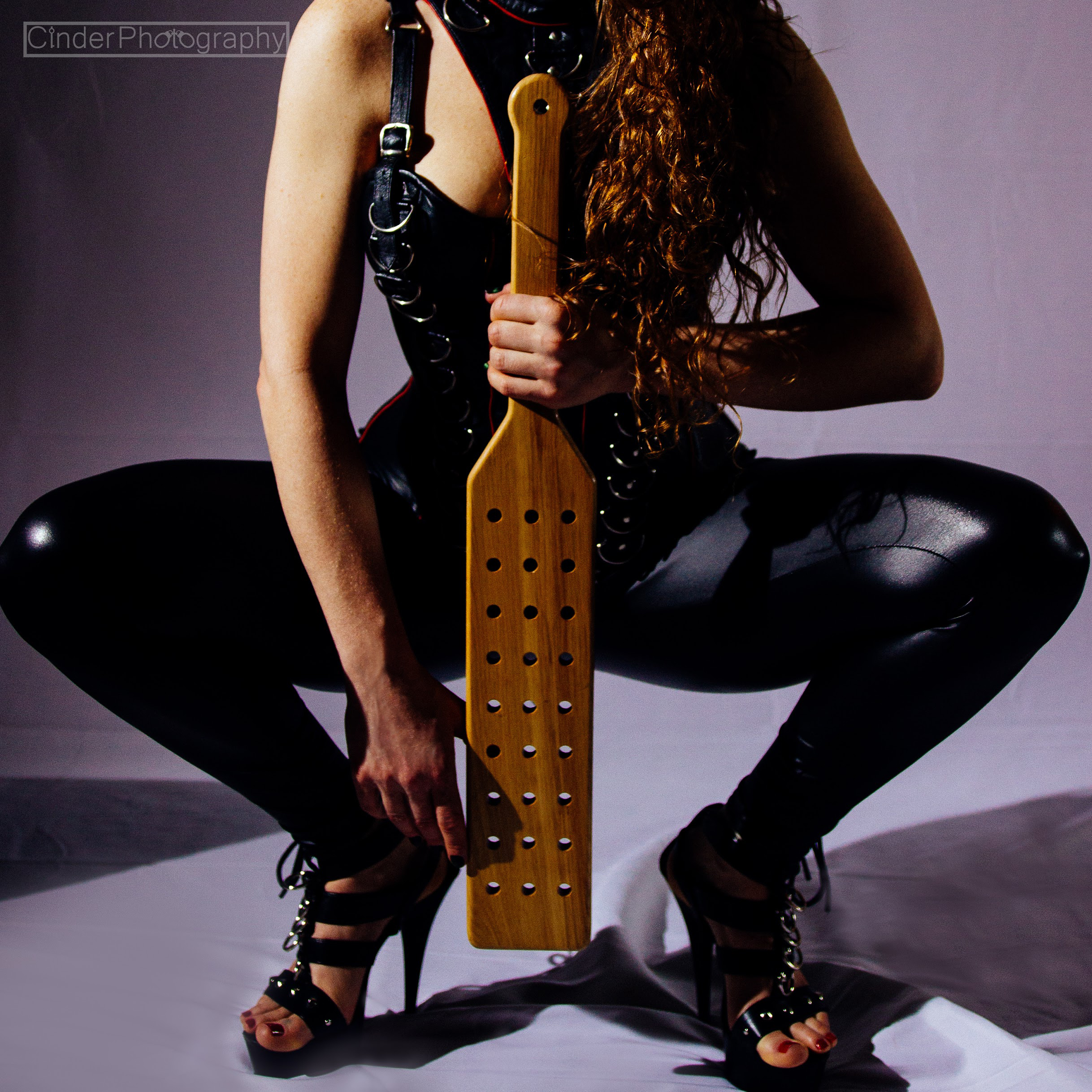 Chicago dominatrix holding long wooden paddle for corporal punishment discipline obedience training masochist sadist sadomasochism